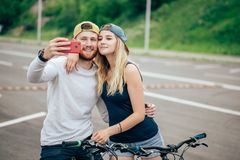 Le couple affectueux prend un selfie sur leur smartphone au centre de la ville Image libre de droits
