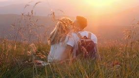 Le couple affectueux se reposant sur un pré de montagne et apprécie la vue du coucher du soleil Images libres de droits
