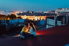 Le couple affectueux se repose sur le toit de la maison Belle soirée photo stock
