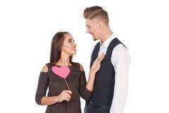 Le couple affectueux souriant et regardant l'un l'autre, la fille tient un coeur sur un bâton Jour du `s de Valentine D'isolement Photographie stock libre de droits