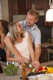 Le couple affectueux sourit à l'un l'autre tout en faisant le dîner ensemble Photos stock