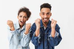 Le couple africain heureux dans des chemises de denim se réjouit ensemble Images libres de droits
