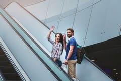 Le couple agréable se tient sur l'escalator avec la valise Images libres de droits