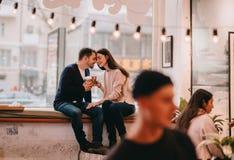 Le couple aimant habillé dans les chandails et des jeans se repose près de l'un l'autre sur le rebord de fenêtre un café et en te images libres de droits