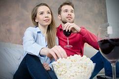 Le couple apprécie le temps gratuit regardant la TV Photographie stock libre de droits