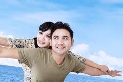 Les couples asiatiques feignent pour voler au-dessus du ciel bleu Photos stock