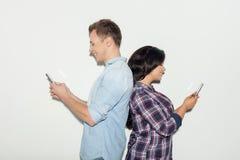 Le couple assez jeune est occupé avec la technologie moderne Photo stock