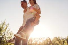 Le couple ayant l'homme de forêt d'amusement au printemps monte son amie dessus de retour au coucher du soleil Image libre de droits