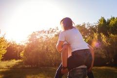 Le couple ayant l'homme de forêt d'amusement au printemps monte son amie dessus de retour au coucher du soleil Types refroidissan Photo stock