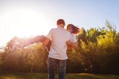 Le couple ayant l'homme de forêt d'amusement au printemps tient son amie dans des mains et tourne au coucher du soleil Types appr Images stock