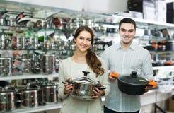 Le couple choisit des casseroles dans le cookware de boutique Photo libre de droits