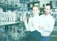 Le couple choisit des verres pour le vin Photographie stock