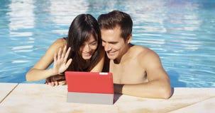 Le couple communique avec des amis sur le dispositif numérique Photographie stock