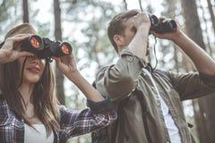 Le couple concentré observe loin utilisant le dispositif spécial Images libres de droits
