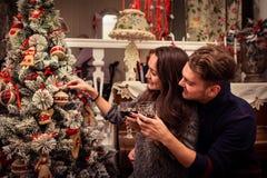 Le couple décore un arbre de Noël ensemble Photo stock