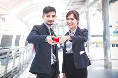 Le couple d'affaires remet tenir un coeur rouge, nous est dans l'amour, healt Photographie stock