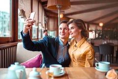 Le couple d'amour étreint et fait le selfie sur l'appareil-photo de téléphone Photo libre de droits