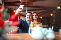 Le couple d'amour étreint et fait le selfie sur l'appareil-photo de téléphone Photographie stock libre de droits