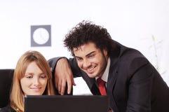 Le couple d'ouvrier utilise l'ordinateur portatif image stock