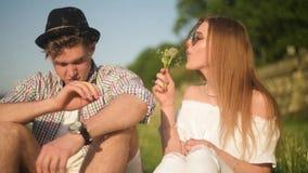 Le couple dans des blowballs de soufflement d'amour fleurit dans les visages de l'un l'autre Personnes de sourire et riantes ayan clips vidéos