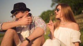 Le couple dans des blowballs de soufflement d'amour fleurit dans les visages de l'un l'autre Personnes de sourire et riantes ayan banque de vidéos