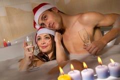 Le couple dans des chapeaux de Santa apprécie un bain Images libres de droits