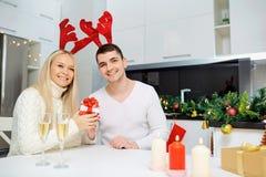 Le couple dans des klaxons de renne donne un cadeau de Noël Photos stock