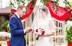 Le couple dans l'échange de vêtement de mariage sonne avec la voûte sur le fond Photo stock