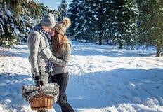 Le couple dans l'amour étreint et marche dans la forêt d'hiver Image libre de droits