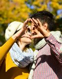 Le couple dans l'amour avec des écharpes montre le signe de coeur Photos stock