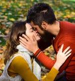 Le couple dans l'amour avec des écharpes se repose sur des feuilles en parc Photo libre de droits