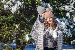 Le couple dans l'amour couvert de couverture étreint dans la forêt d'hiver Image libre de droits