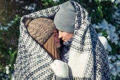 Le couple dans l'amour couvert de couverture étreint dans la forêt d'hiver Images stock