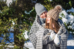 Le couple dans l'amour couvert de couverture étreint dans la forêt d'hiver Photo stock