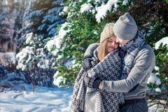 Le couple dans l'amour couvert de couverture étreint dans la forêt d'hiver Images libres de droits