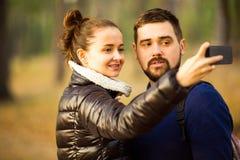 Le couple dans l'amour en automne fait le selfie Photos stock