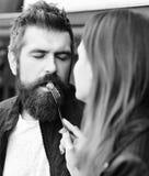 Le couple dans l'amour mange des baies La fille alimente le type barbu avec la framboise sur la fourchette Image libre de droits