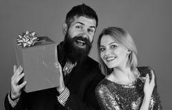 Le couple dans l'amour partage des présents sur le fond rouge Photos libres de droits