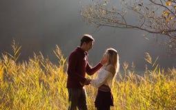 Le couple dans l'amour regardant un l'un l'autre dans les domaines des roseaux/des jeunes couples regardant dans l'un l'autre le  Photo libre de droits