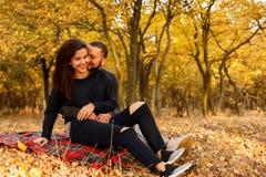 Le couple dans l'amour se reposant l'automne tombé part dans un parc Images libres de droits