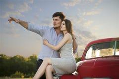 Le couple dans l'amour se repose sur d'une rétro des points voiture et d'homme à la distance par sa main Photos stock