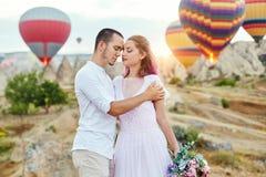 Le couple dans l'amour se tient sur le fond des ballons dans Cappadocia Équipez et une femme sur le regard de colline à un grand  Images libres de droits