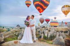 Le couple dans l'amour se tient sur le fond des ballons dans Cappadocia Équipez et une femme sur le regard de colline à un grand  Photo stock