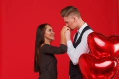 Le couple dans l'amour, type embrasse une main du ` s de fille, à côté des boules sous forme de coeur Fond rouge Image stock