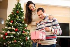 Le couple dans l'ouverture d'amour présente près de l'arbre de Noël Photos libres de droits