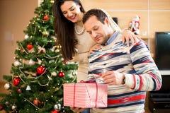 Le couple dans l'ouverture d'amour présente près de l'arbre de Noël Image stock