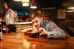 Le couple dans la querelle, homme mange au compteur de barre images libres de droits