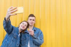 le couple dans la veste de denim fait le selfie sur un fond jaune images stock