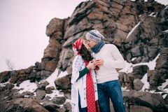 Le couple dans les chapeaux, les écharpes et des jeans humides avec des tasses de thé chaud dans leurs mains embrasse pendant la  Photo libre de droits