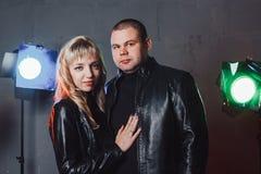 Le couple dans le noir s'habille pendant le tir d'image dans le studio et les projecteurs Image libre de droits